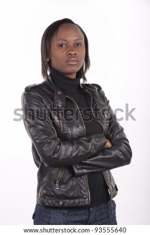 Young South African woman wearing black leather and a serious expression on a white background. - stock photo