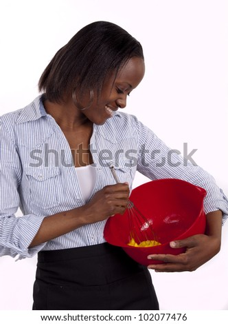 Young South African woman whisking an egg with a smile - stock photo