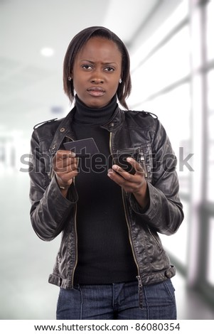 Young South African woman with a worried expression about her finances, holding a credit card, and doing a mobile phone transaction. - stock photo