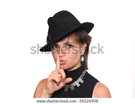 Young spanish-looking girl in a black hat with finger to mouth