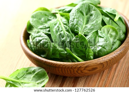 Young spinach in a wooden plate - stock photo