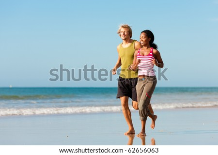 Young sport couple - Caucasian man and African-American woman - jogging on the beach - stock photo