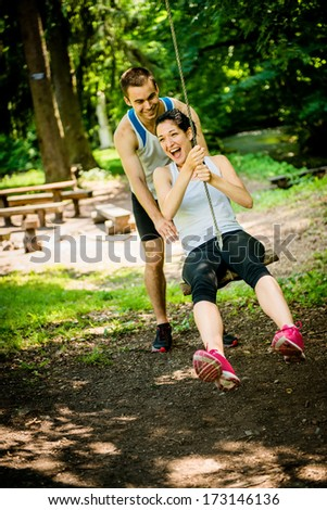 Young sport couple having fun - swinging on seesaw - stock photo