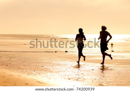 Young sport couple - jogging on the beach in sunset - stock photo
