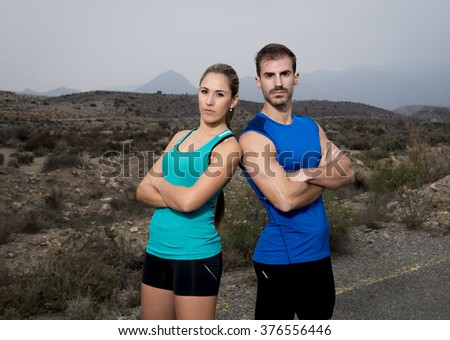 young sport couple posing shoulder to shoulder looking cool and defiant attitude girl wearing cyan tank top and man blue singlet both with folded arms in fitness club advertising style