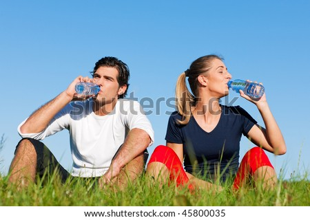 Young sport couple was jogging on a green summer meadow but is resting now, replenishing themselves with a zip of water - stock photo