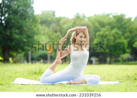 Young sport girl do yoga in the park, asian beauty woman - stock photo