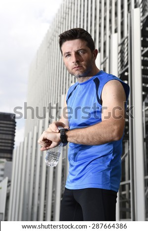 young sport man checking time on chrono timer runners watch holding water bottle after training session in business district with urban office building background in fitness concept