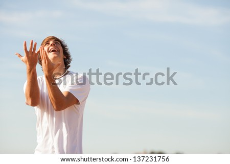 young sport man playing rugby on the beach - stock photo