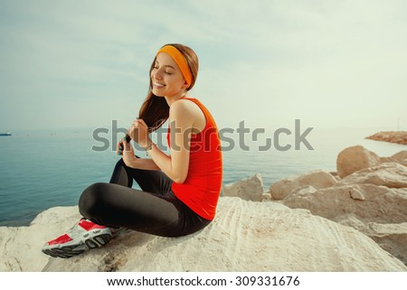 Young sport woman in red shirt and sneakers sitting on the rocky beach in the morning. Photo with cross processing filter - stock photo