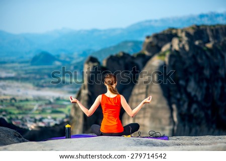Young sport woman meditating on the mat in the mountains. Back view - stock photo