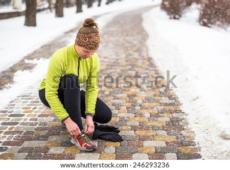 Young sport woman  tying running shoes during winter training outside in cold snow weather in park  - stock photo