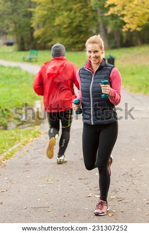 Young sportage girl running with dumbbells in park - stock photo
