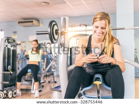 Young sporting woman texting with smartphone in a gym - Concepts about lifestyle and sport in a fitness club - stock photo