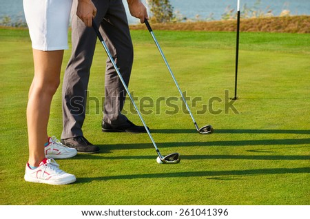 Young sportive couple playing golf on a golf course. Close up - stock photo