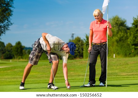 Young sportive couple playing golf on a golf course, he takes the ball from the hole - stock photo