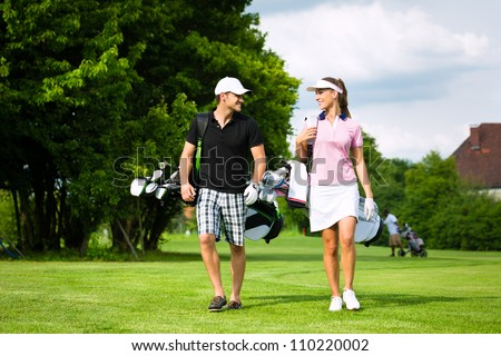 Young sportive couple playing golf on a golf course, they walking to the next hole