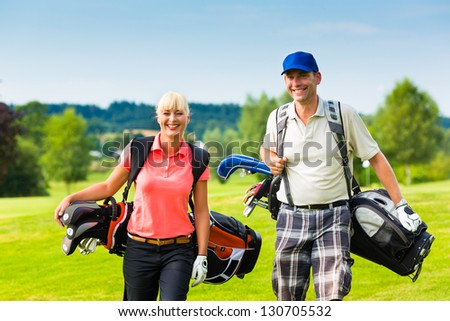 Young sportive couple playing golf on a golf course, they walking to the next hole - stock photo