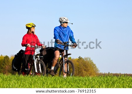 Young sportive couple with mountain bikes having fun