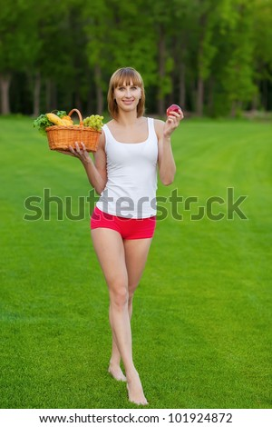 Young sportive woman with basket of fruits after fitness exercise - stock photo