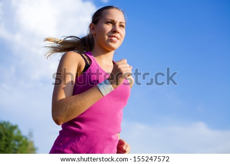 Young sports girl runs on a background of blue sky - stock photo