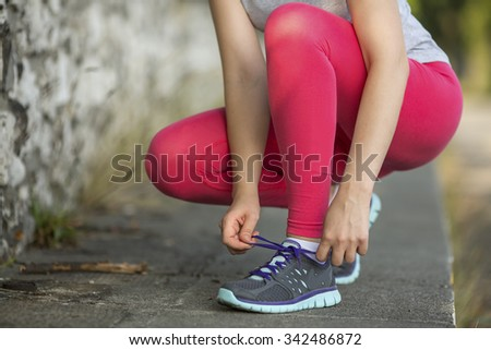 Young sports girl tying shoelaces on cross-country sneakers outdoors.