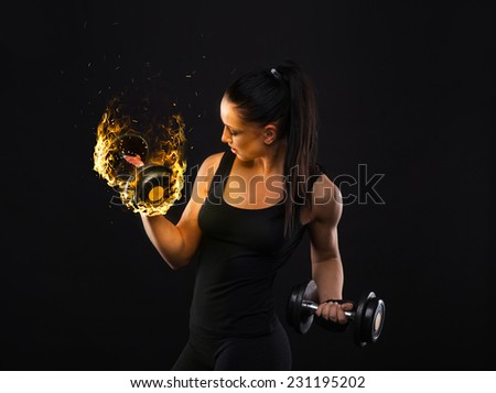 Young sports-looking nice lady with dark hair shows various performs exercises with equipment on the black background in studio - stock photo