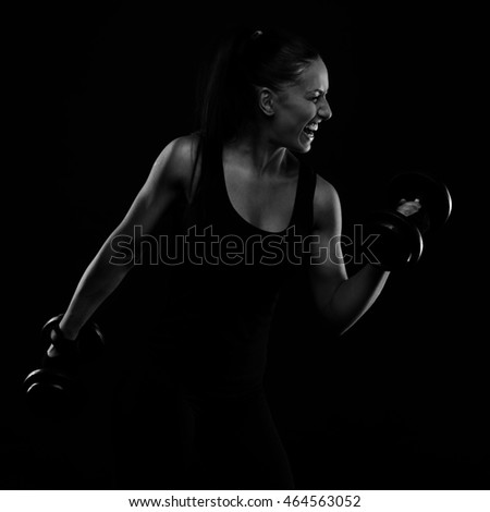 Young sports-looking nice lady with dark hair shows various performs exercises with equipment on the black background in studio