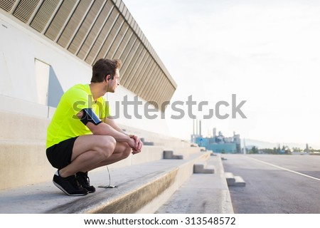 Young sports man thoughtful looking away while having a rest after workout training outdoors in urban setting, male runner listen to music in headphones though smart phone and admiring morning sunrise - stock photo