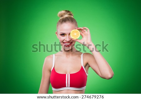 Young sports sexy girl in the studio on a green background with fresh fruit - stock photo