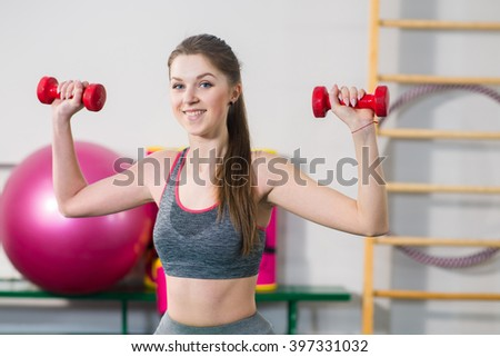 young sports woman doing exercises with dumbells at the gym