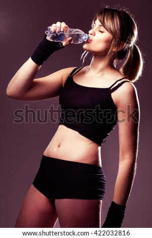 young sports woman drinks water in studio