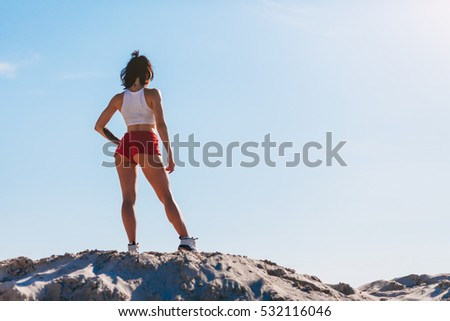 Young sports woman in red shorts and a white top standing on the hill on a background of blue sky and posing