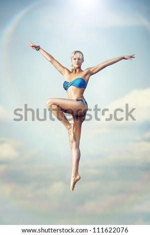 Young sports woman jumping up high.