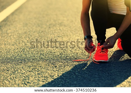 young sports woman runner tying shoelace on city road - stock photo