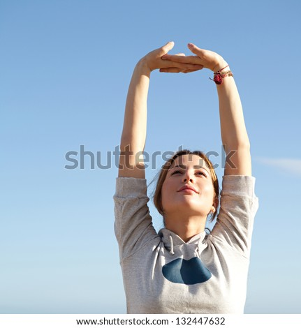 Young sports woman stretching her arms up with interlinked fingers while exercising on a beach with a blue sky and the sea in the background. - stock photo
