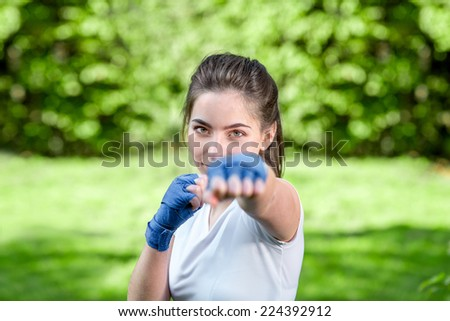 Young sports woman with bandage on her hands boxing in the park - stock photo