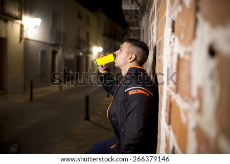 Young sportsman drinking energy drink in the street in urban night