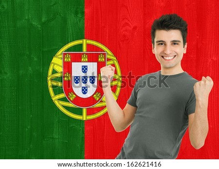 young sportsman fan cheering against the Portuguese flag - stock photo