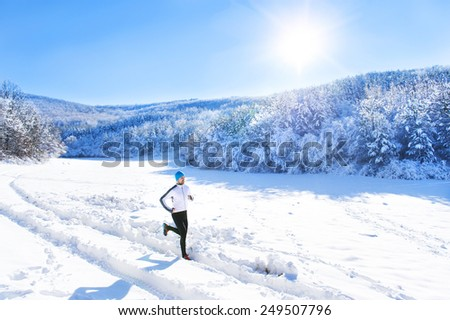 Young sportsman jogging outside in sunny winter park - stock photo