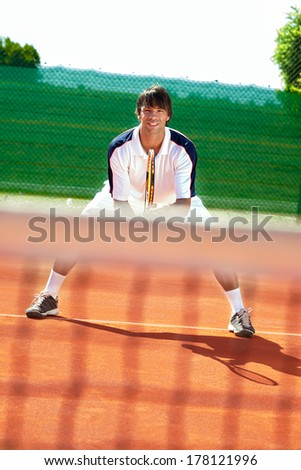 young sportsman playing tennis on tennis court - stock photo