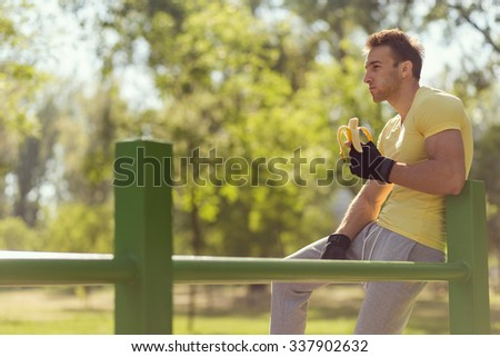 Young sportsman sitting on a bar in an outdoor gym, eating a banana - stock photo