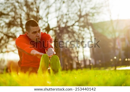 Young sportsman working-out in a park, stretching hamstrings before running - stock photo