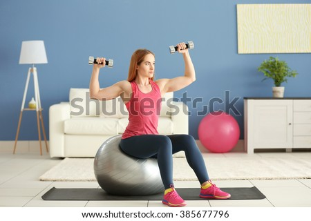 Young sportswoman doing exercises with ball and dumbbells on a mat at home - stock photo