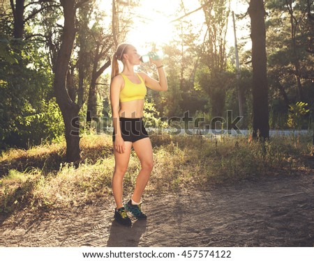 Young sportswoman drinking water after run, sport exercises, fitness. Beautiful sporty girl resting at sunset in summer forest. Fitness model workout. Beautiful fitness athlete woman with water bottle