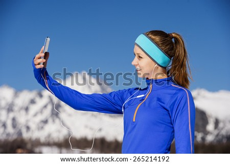 Young sportswoman jogging outside in sunny winter mountains taking selfie. - stock photo