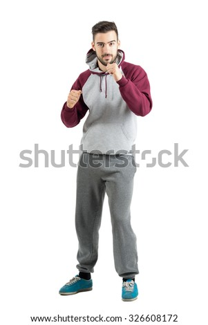 Young sporty casual man in sportswear with boxing hand gesture. Full body length portrait isolated over white studio background. - stock photo