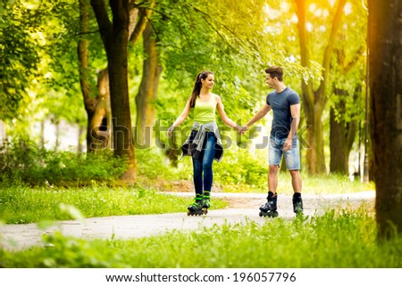 Young sporty couple ride rollerblades  and enjoying in nature  - stock photo