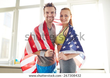 Young sporty couple wrapped in USA flag - stock photo