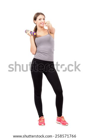 Young sporty fitness woman holding dumbbell pointing at you. Full body length portrait isolated over white background. - stock photo